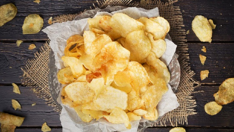 A bowl of potato chips on a rustic table.