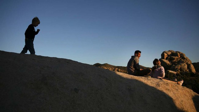 Aaron Stubbs, second from right, and his two children sit on a rock to watch sunset at Joshua Tree National Park in California, Tuesday, May 19, 2020. The park reopened this week after a lengthy closure to help slow the spread of the new coronavirus. (AP Photo/Jae C. Hong)