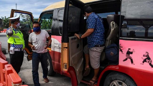 Petugas Polresta Cirebon mengarahkan pemudik untuk diperiksa suhu tubuh saat melintas di pintu Tol Cipali Palimanan, Cirebon, Jawa Barat, Kamis (21/5/2020). Pemeriksaan tersebut sebagai upaya penyekatan gelombang pemudik jelang perayaan Hari Raya Idul Fitri 1441 H dari arah Jakarta menuju Jawa Tengah. ANTARA FOTO/Nova Wahyudi/nz
