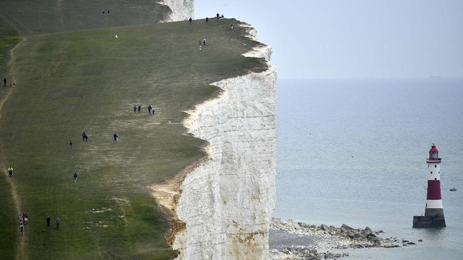 People walk along the cliff-top above the lighthouse at Beachy Head near Eastbourne on the south coast of England on May 17, 2020, following an easing of lockdown rules in England during the novel coronavirus COVID-19 pandemic. - People are being asked to