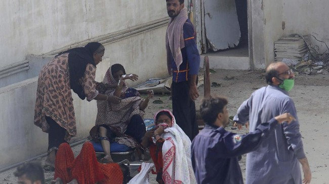 Residents of an area hit by a plane crash wait for medical help in Karachi, Pakistan, Friday, May 22, 2020. An aviation official says a passenger plane belonging to state-run Pakistan International Airlines carrying more than 100 passengers and crew has crashed near the southern port city of Karachi. (AP Photo/Fareed Khan)