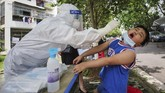 This photo taken on May 16, 2020 shows a medical worker taking a swab sample from a child to be tested for the COVID-19 coronavirus, in a street in Wuhan, in China's central Hubei province. (Photo by STR / AFP) / China OUT