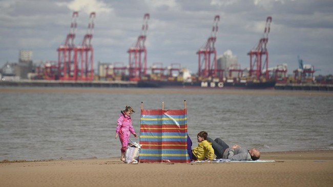 A family enjoys the sunshine on New Brighton Beach, Merseyside in north west England on May 16, 2020, following an easing of lockdown rules in England during the novel coronavirus COVID-19 pandemic. - People are being asked to