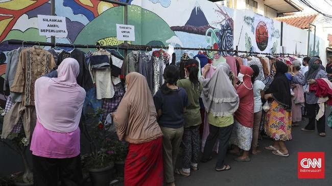 Warga memilih baju bekas layak pakai hasil sumbangan di RT 02 RW 04 Kelurahan Jati Padang, Jakarta, Jumat, 22 Mei 2020. Pakaian bekas layak pakai gratis tersebut diperuntukan bagi warga yang membutuhkan karena terdampak penerapan Pembatasan Sosial Berskala Besar (PSBB) untuk pencegahan COVID-19 di DKI Jakarta yang berimbas pada berkurangnya pendapatan mereka. CNNIndonesia/Safir Makki