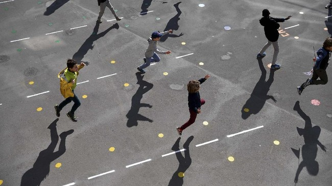Pupils play in the school yard of the Saint Germain de Charonne school in Paris on May 14, 2020, as primary schools in France re-open this week and the country eases lockdown measures taken to curb the spread of the COVID-19 (the novel coronavirus). (Photo by FRANCK FIFE / AFP)