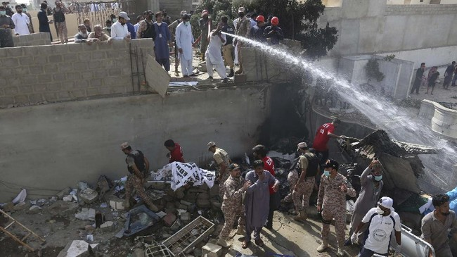 Soldiers and volunteers collect dead bodies at the site of a crash in Karachi, Pakistan, Friday, May 22, 2020. An aviation official says a passenger plane belonging to state-run Pakistan International Airlines carrying more than 100 passengers and crew has crashed near the southern port city of Karachi. (AP Photo/Fareed Khan)
