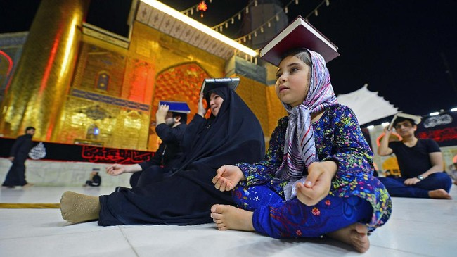 Shiite Muslims gather, albeit in fewer numbers due to the COVID-19 pandemic, at the Imam Ali shrine in the central Iraqi holy city of Najaf late on May 16, 2020, to mark Lailat al-Qadr, a night in the holy month of Ramadan during which the Koran was first revealed to the Prophet Mohammed in the seventh century. - Worshippers placed copies of the Koran on their heads to convey veneration during the overnight prayers in a centuries-old ritual, as they pleaded to God to rid them of the ongoing novel coronavirus pandemic. (Photo by Haidar HAMDANI / AFP)