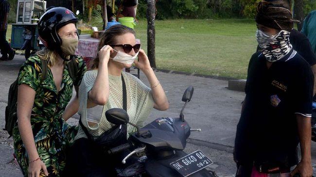 Pecalang meminta wisatawan mancanegara untuk mengenakan masker sebagai upaya pencegahan penyebaran COVID-19 di wilayah Desa Adat Jimbaran, Badung.