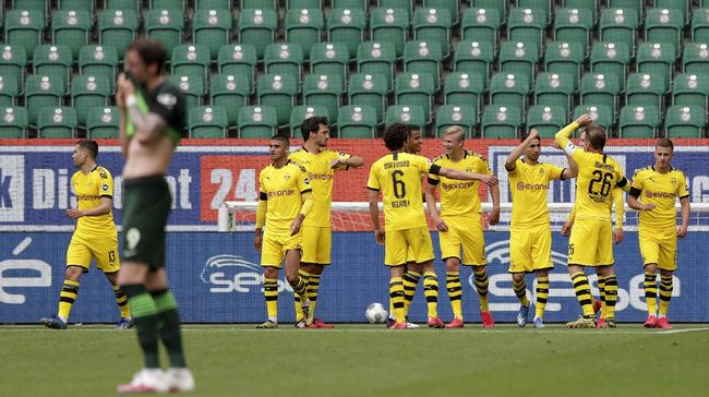 Dortmund player celebrate after Raphael Guerreiro, far left, scored the opening goal during the German Bundesliga soccer match between VfL Wolfsburg and Borussia Dortmund in Wolfsburg, Germany, Saturday, May 23, 2020. The German Bundesliga is the world's first major soccer league to resume after a two-month suspension because of the coronavirus pandemic. (AP Photo/Michael Sohn, Pool)