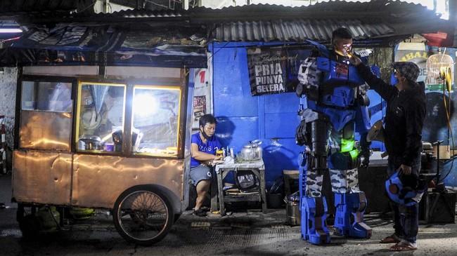 Warga yang menggunakan kostum Robot Sikopit berbuka puasa di sela patroli di sekitaran Pasar Cikutra, Bandung, Jawa Barat, Senin (4/5/2020).