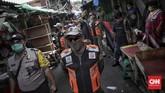 Petugas gabungan dari Satpol PP dan Polsek Tanah Abang melakukan penertiban dengan menghimbau terhadap pedagang Pasar Tanah Abang agar segera menutup kiosnya, Jakarta, Sabtu, 23 Mei 2020. Penertiban tersebut dilakukan guna memutus rantai penyebaran virus Covid-19. CNN Indonesia/Bisma Septalisma