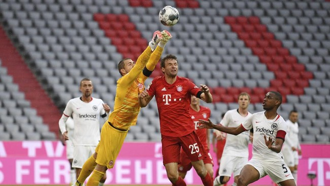 Bayern Munich's Thomas Muller in action with Eintracht Frankfurt's Kevin Trapp during the German Bundesliga soccer match between Bayern Munich and Eintracht Frankfurt in Munich, Germany, Saturday, May 23, 2020. (Andreas Gebert/pool via AP)