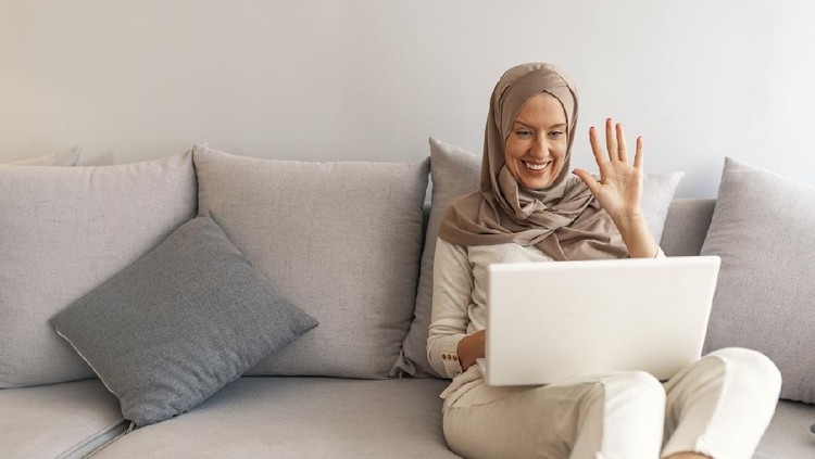 Young Muslim woman having video call via laptop at home. Happy smiling Muslim woman sitting on sofa, couch and using laptop at living room at home, learning language, video calling.