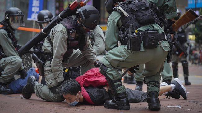 Riot police detain a protester during a demonstration against Beijing's national security legislation in Causeway Bay in Hong Kong, Sunday, May 24, 2020. Hong Kong police fired volleys of tear gas in a popular shopping district as hundreds took to the streets Sunday to march against China's proposed tough national security legislation for the city. (AP Photo/Vincent Yu)