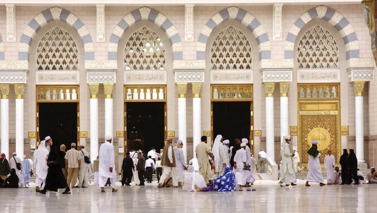 Medina, Saudi Arabia - April 16, 2011: Muslim pilgrims entering to Masjid al-Nabawi ( Prophet's Mosque ) for the noon prayer. As the final resting place of the Prophet Muhammad, it is considered the second holiest site in Islam by Muslims (the first being the Masjid al-Haram in Mecca).