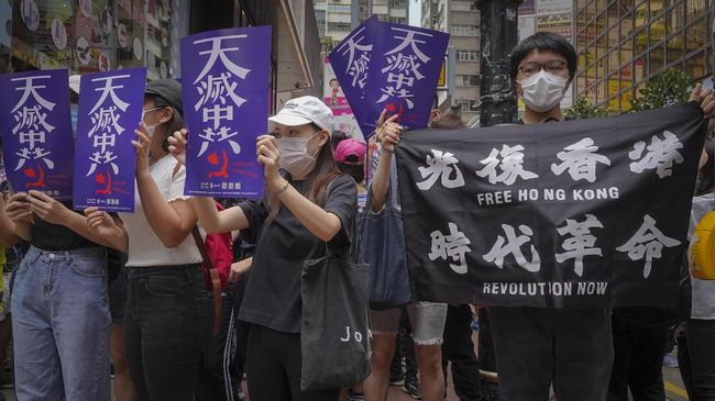 Hundreds of protesters with banners march along a downtown street during a pro-democracy protest against Beijing's national security legislation in Hong Kong, Sunday, May 24, 2020. Hong Kong's pro-democracy camp has sharply criticised China's move to enact national security legislation in the semi-autonomous territory. They say it goes against the