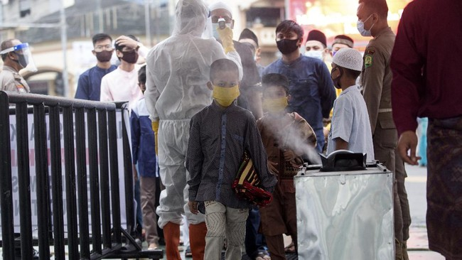A boy walks past a disinfectant sprayer at the Al Mashun Grand Mosque to attend Eid al Fitr prayer amid concerns of coronavirus outbreak in Medan, North Sumatra, Indonesia, Sunday, May 24, 2020. Millions of people in the world's largest Muslim nation are marking a muted and gloomy religious festival of Eid al-Fitr, the end of the fasting month of Ramadan _ a usually joyous three-day celebration that has been significantly toned down as coronavirus cases soar. (AP Photo/Binsar Bakkara)