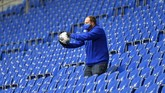 A ball boy gets a ball from the empty tribune prior the German Bundesliga soccer match between FC Schalke 04 and FC Augsburg at the Veltins-Arena in Gelsenkirchen, Germany, Sunday, May 24, 2020. The German Bundesliga becomes the world's first major soccer league to resume after a two-month suspension because of the coronavirus pandemic. (AP Photo/Martin Meissner, Pool)