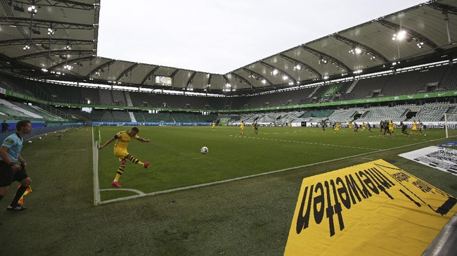 Dortmund's Raphael Guerreiro takes a corner kick during the German Bundesliga soccer match between VfL Wolfsburg and Borussia Dortmund in Wolfsburg, Germany, Saturday, May 23, 2020. The German Bundesliga is the world's first major soccer league to resume after a two-month suspension because of the coronavirus pandemic. (AP Photo/Michael Sohn, Pool)