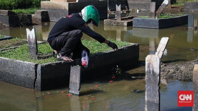 Warga melakukan ziarah kubur hari kedua Idul Fitri di TPU Semper, Jakarta Utara, Senin, 25 Mei 2020. Meskipun PSBB masih berlangsung di DKI Jakarta, warga tak surut mendatangi TPU melakukan tradisi ziarah. CNNIndonesia/Safir Makki