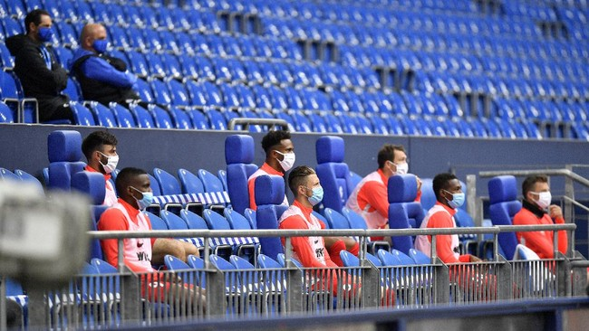 Augsburg alternate players sit on the bench during the German Bundesliga soccer match between FC Schalke 04 and FC Augsburg at the Veltins-Arena in Gelsenkirchen, Germany, Sunday, May 24, 2020. The German Bundesliga becomes the world's first major soccer league to resume after a two-month suspension because of the coronavirus pandemic. (AP Photo/Martin Meissner, Pool)