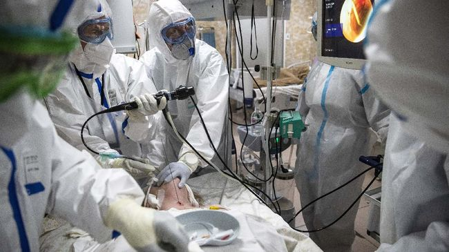 Medical workers wearing special suits to protect against coronavirus perform tracheal intubation of a coronavirus patient being on artificial lung respiration at an intensive care unit of the Filatov City Clinical Hospital in Moscow, Russia, Friday, May 15, 2020. Russian capital, with a population of more than 12 million, accounts for half of the country's more than 262,000 reported infections. (AP Photo/Pavel Golovkin)