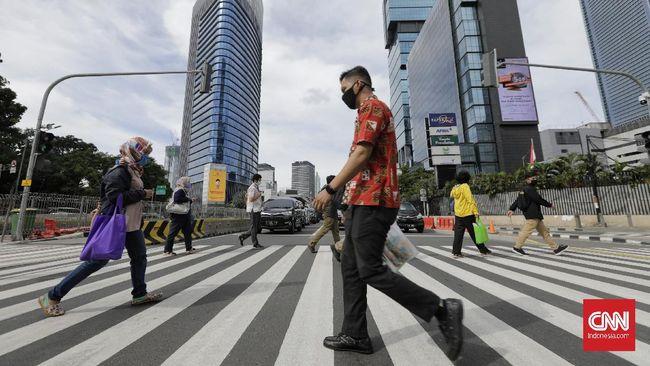 Sejumlah pekerja berjalan dengan latar belakang gedung perkantoran, Jakarta, Kamis (16/4/2020). H+2 lebaran jalan Jakarta terpantau ramai selama masa Pembatasan Sosial Berskala Besar (PSBB) tahap tiga di Jakarta. (CNN Indonesia/ Adhi Wicaksono)