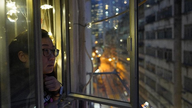 Associated Press reporter Zen Soo pokes her head out the window for some fresh air while serving her 14-day quarantine at home in Hong Kong, April 17, 2020. Hong Kong issued quarantine wristbands to monitor returning residents of the city while they serve their mandatory 14-day quarantine, in a bid to curb local transmissions of COVID-19 during the pandemic. (AP Photo/Vincent Yu)