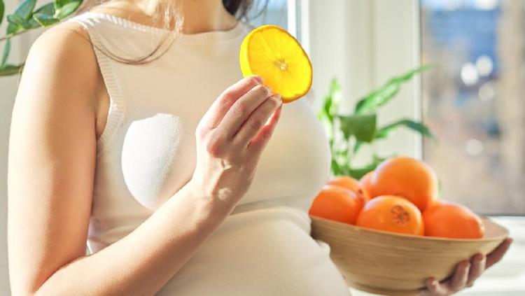 Ilustrasi wanita hamil makan jeruk atau buah