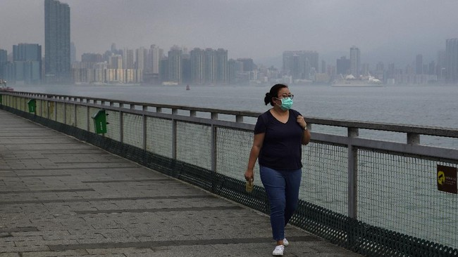 Associated Press reporter Zen Soo walks along the Quarry Bay Promenade in Hong Kong on the first day of freedom after 14 days of home quarantine in Hong Kong, April 19, 2020. (AP Photo/Vincent Yu)