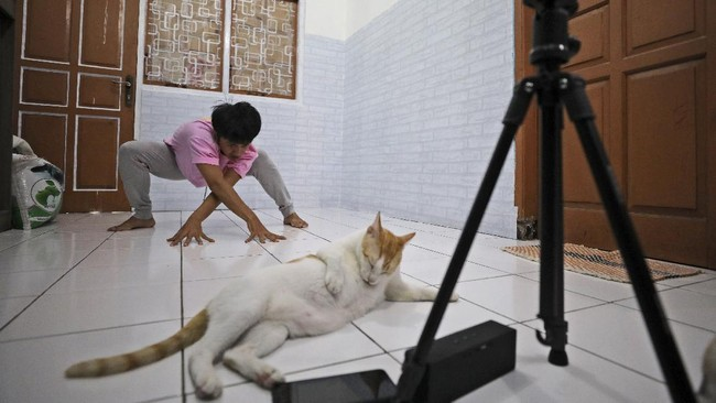 Dancer Siko Setyanto performs a dance while recording it using an action camera mounted on a tripod at his one-bedroom rented house in Jakarta, Indonesia Thursday, May 14, 2020. Two Indonesian choreographers are helping fellow dancers who lost their jobs due to the new coronavirus outbreak in the country by setting up a YouTube channel as a platform where dancers, choreographers and dance teachers can perform, then receive donation from viewers. (AP Photo/Dita Alangkara)