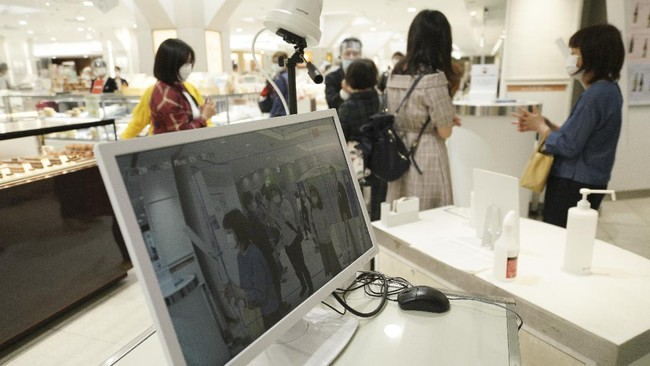 A thermography camera monitors as the customers enter a building Monday, May 25, 2020, in Tokyo. Japan's Prime Minister Shinzo Abe is expected to remove a coronavirus state of emergency from Tokyo and four other remaining prefectures later in the day. (AP Photo/Eugene Hoshiko)