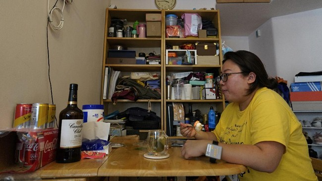 Associated Press reporter Zen Soo eats her lunch at the dining table at home while serving a two-week home quarantine in Hong Kong, April 17, 2020. Hong Kong issued quarantine wristbands to monitor returning residents of the city while they serve their mandatory 14-day quarantine, in a bid to curb local transmissions of COVID-19 during the pandemic. (AP Photo/Vincent Yu)
