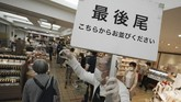An employee holds a sign to show the last in the queue as shoppers maintain a safe social distance between each other as they wait in line for casher at a food section of the Matsuya Ginza department store which partially reopens Monday, May 25, 2020, in Tokyo. Japan's Prime Minister Shinzo Abe is expected to remove a coronavirus state of emergency from Tokyo and four other remaining prefectures later in the day. Japanese words read as