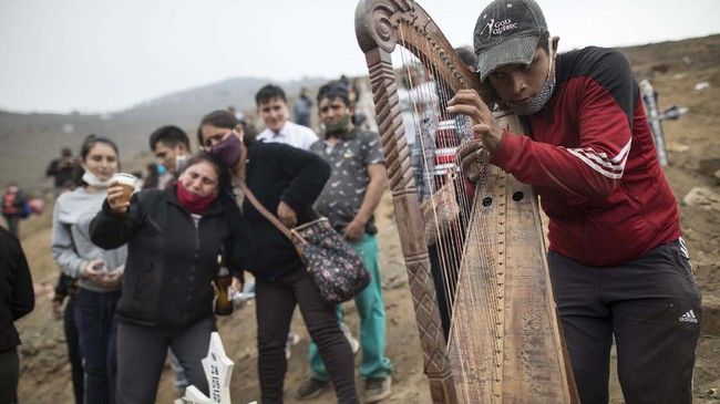 Harpist and cemetery worker Charlie Juarez performs while Gregoria Zumaeta, 44, left, mourns the death of her brothers Jorge Zumaeta, 50, and Miguel Zumaeta, 54, who died from COVID-19, at the Nueva Esperanza cemetery on the outskirts of Lima, Peru, Tuesday, May 26, 2020. (AP Photo/Rodrigo Abd)
