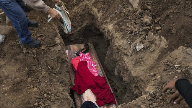 Relatives put clothes belonging to Felicia Maldonado who died from COVID-19, over her coffin at the Nueva Esperanza cemetery on the outskirts of Lima, Peru, Tuesday, May 26, 2020. (AP Photo/Rodrigo Abd)