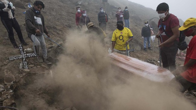 Cemetery workers try bury the coffin with the corpse of Flavio Juarez, 50, who died from COVID-19, at the Nueva Esperanza cemetery on the outskirts of Lima, Peru, Tuesday, May 26, 2020. (AP Photo/Rodrigo Abd)