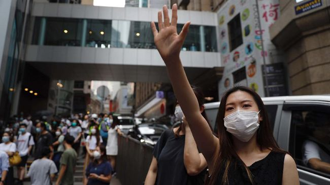 A protester gestures with five fingers, signifying the