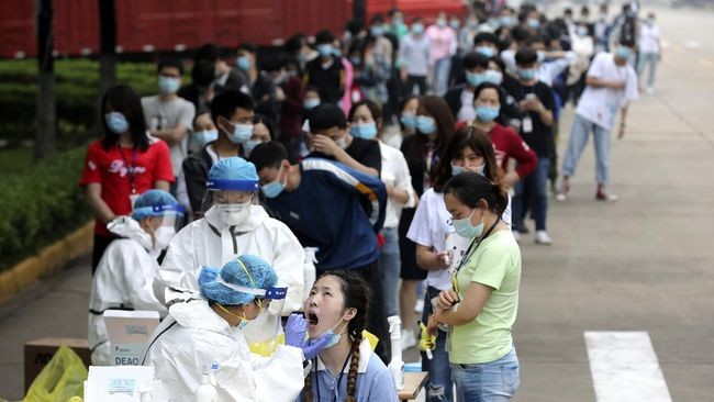 Workers line up for medical workers to take swabs for the coronavirus test at a large factory in Wuhan in central China's Hubei province Friday, May 15, 2020. Wuhan have begun testing inhabitants for the coronavirus as a program to test everyone in the Chinese city of 11 million people in 10 days got underway. (Chinatopix Via AP)