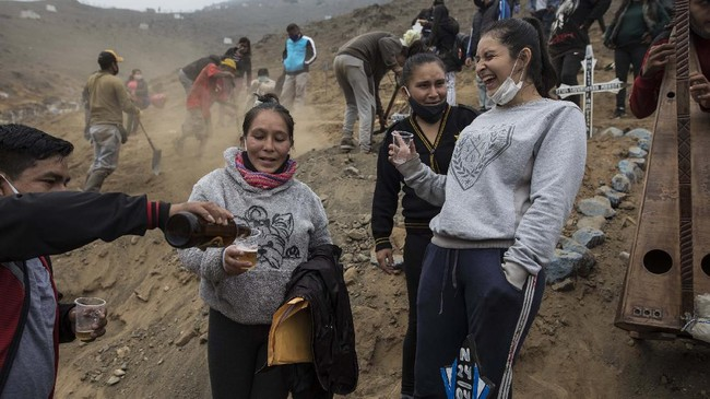 Relatives of brothers Jorge Zumaeta, 50, and Miguel Zumaeta, 54, who died from COVID-19, drink beer and make jokes during their burial at the Nueva Esperanza cemetery on the outskirts of Lima, Peru, Tuesday, May 26, 2020. (AP Photo/Rodrigo Abd)