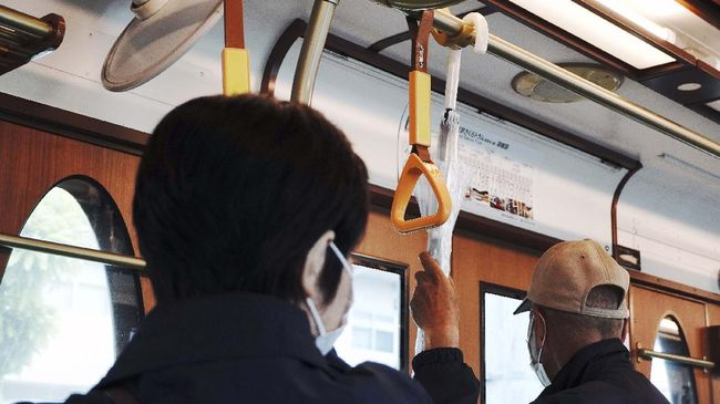 A man wearing a face mask holds on an umbrella next to an unused strap on a tramcar Wednesday, May 20, 2020, in Tokyo. Japan's prime minister has announced the end of the state of emergency for most regions of the country, but restrictions are being kept in place in Tokyo and seven other high-risk areas, including Osaka, Kyoto and Hokkaido. (AP Photo/Eugene Hoshiko)