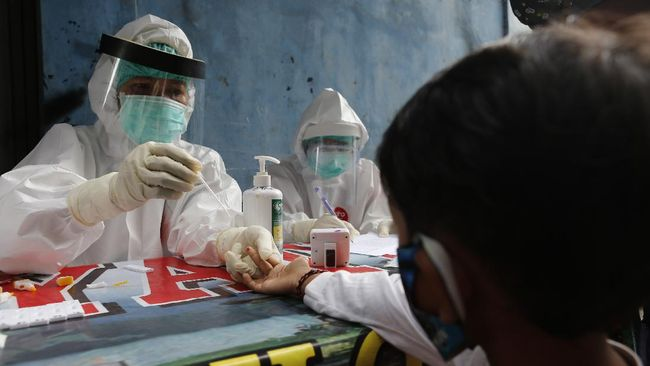 A coronavirus antibody test from health workers at a village in Bali, Indonesia, Wednesday, May 27, 2020. (AP Photo/Firdia Lisnawati)