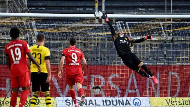 Dortmund's Swiss goalkeeper Roman Buerki (R) fails to keep out the opening goal scored by Bayern Munich's German midfielder Joshua Kimmich (not in picture) during the German first division Bundesliga football match BVB Borussia Dortmund v FC Bayern Munich on May 26, 2020 in Dortmund, western Germany. (Photo by Federico GAMBARINI / POOL / AFP) / DFL REGULATIONS PROHIBIT ANY USE OF PHOTOGRAPHS AS IMAGE SEQUENCES AND/OR QUASI-VIDEO