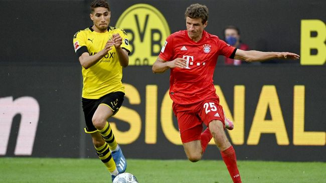 Bayern Munich's German forward Thomas Mueller (R) and Dortmund's Moroccan defender Achraf Hakimi vie for the ball during the German first division Bundesliga football match BVB Borussia Dortmund v FC Bayern Munich on May 26, 2020 in Dortmund, western Germany. (Photo by Federico GAMBARINI / POOL / AFP) / DFL REGULATIONS PROHIBIT ANY USE OF PHOTOGRAPHS AS IMAGE SEQUENCES AND/OR QUASI-VIDEO