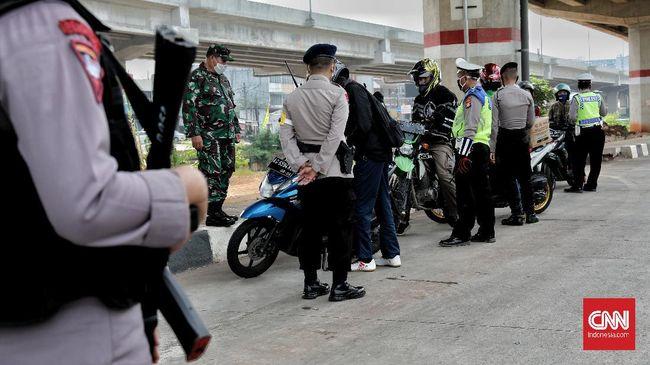 Petugas gabungan (TNI, Polisi, Satpol PP) melakukan pengecekan surat izin keluar masuk (SIKM)  Jakarta bagi pengendara motor dan mobil di check point Lampiri, Jakarta Timur, Rabu, 27 Mei 2020. Bagi pengendara mobil maupun motor yang ber-plat diluar Jabodetabek dan tak dapat menunjukkan SIKM diwajibkan memutar balik kendaraan. CNNIndonesia/Safir Makki