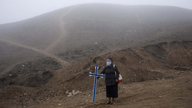 Noly Suarez, 53, holds a cross during the burial of her brother Flavio Juarez, 50, who died from COVID-19, at the Nueva Esperanza cemetery on the outskirts of Lima, Peru, Tuesday, May 26, 2020. (AP Photo/Rodrigo Abd)