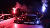Fans light up flares as they celebrate after watching the Czech first division soccer match between Viktoria Plzen and Sparta Praha at a drive-in movie theater in Pilsen, Czech Republic, Wednesday, May 27, 2020. The match is being played live where fans can watch it on the screen at the drive in theater due to the highly contagious coronavirus. (AP Photo/Petr David Josek)