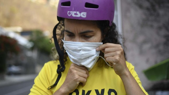 Venezuelan Olympic medalist Stefany Hernandez, a BMX racing cyclist, puts on a face mask amid the COVID-19 pandemic before training in Caracas, Venezuela, Saturday, April 25, 2020. Despite a quarantine to curb the spread of the new coronavirus, Hernandez trains three times a week in hopes of qualifying for the 2021 Tokyo Summer Olympics. (AP Photo/Matias Delacroix)