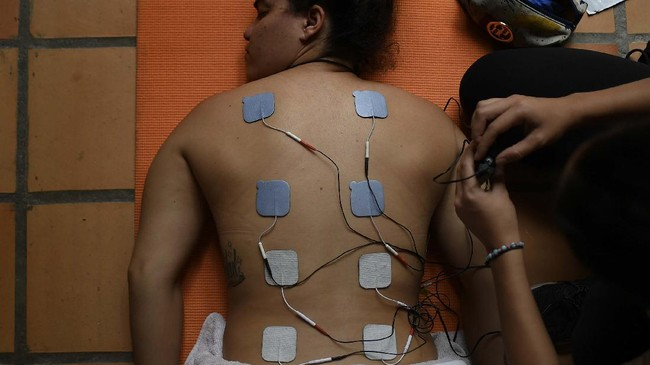 Venezuelan Olympic medalist Stefany Hernandez, a BMX racing cyclist, receives electro-stimulation pads on her back during a muscle relaxation session with her physical therapist at her home in Caracas, Venezuela, Monday, May 25, 2020. Despite a quarantine to curb the spread of COVID-19, Hernandez trains three times a week in hopes of qualifying for the 2021 Tokyo Summer Olympics. (AP Photo/Matias Delacroix)