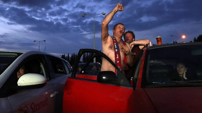 Fans cheer as they watch the Czech first division soccer match between Viktoria Plzen and Sparta Praha at a drive-in movie theater in Pilsen, Czech Republic, Wednesday, May 27, 2020. The match is being played live where fans can watch it on the screen at the drive in theater due to the highly contagious coronavirus. (AP Photo/Petr David Josek)